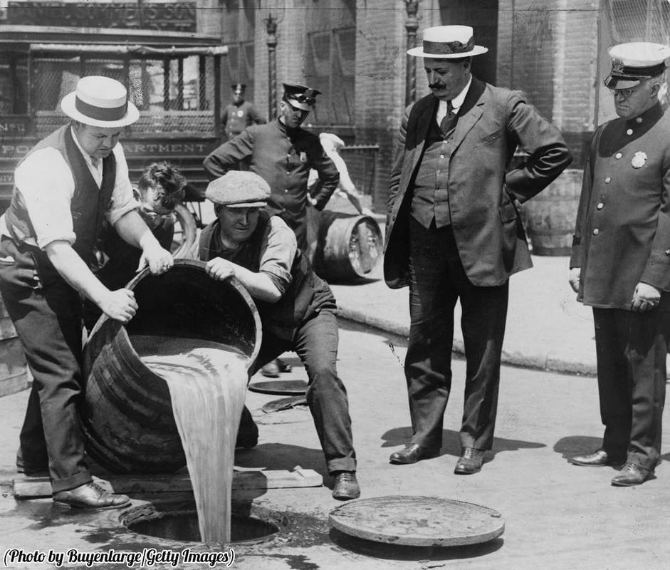 Agentes de Nova Iorque despejando álcool no esgoto após uma apreensão durante o auge da proibição, por volta de 1921