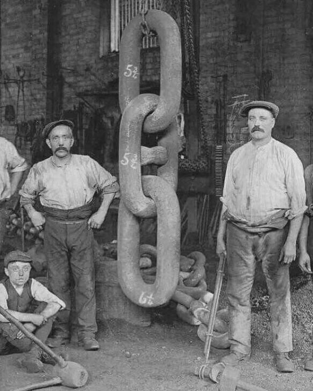 Homens ao lado dos gigantes elos forjados para a âncora do Titanic, em 1910