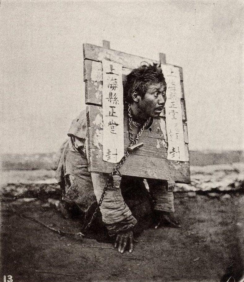 Homem usa uma placa de madeira em volta do pescoço como forma de punição por ter cometido um crime em Xangai, China, em 1874