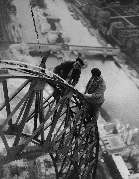 Eletricistas instalando luzes na Torre Eiffel sem nenhuma proteção adicional, em 1937