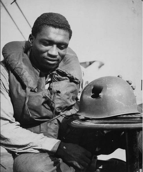 Guarda costiero mostra como ficou seu capacete após ser atingido por estilhaços durante desembarque dos aliados na França, em 1944
