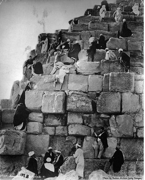 Turistas escalando uma pirâmide no Egito, nos anos 1800