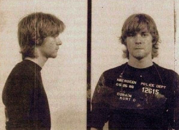 """Kurt Cobain, quando ainda não era cantor, preso por pichar muros com a frase """"Deus é gay"""", em 1986"""