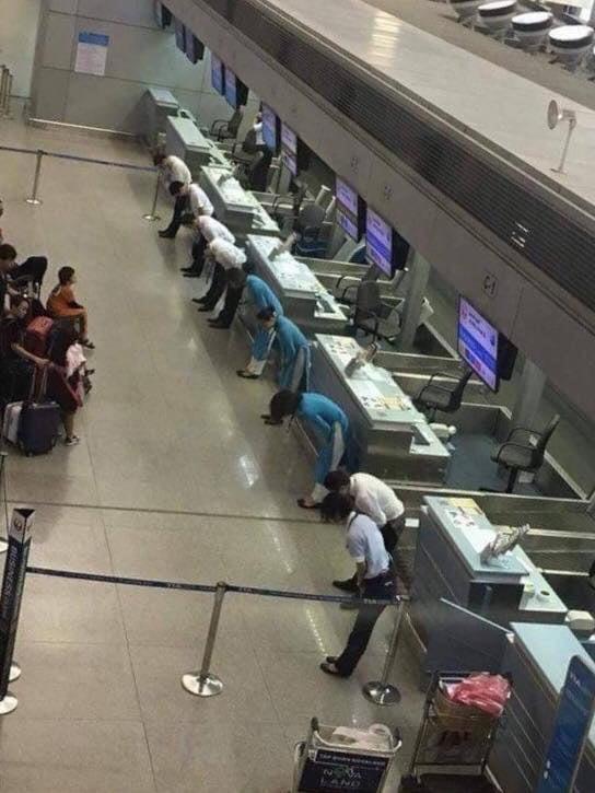Funcionários de uma companhia aérea japonesa curvando-se para pedir desculpas aos passageiros pelo atraso nos vôos