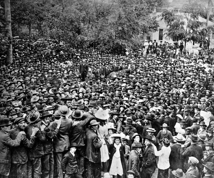 Multidão se reúne para testemunhar o enforcamento de Henry Campbell, julgado e condenado por assassinar uma mulher e sua filha. Ele está de pé ao centro vestindo um terno escuro, Georgia, 1908