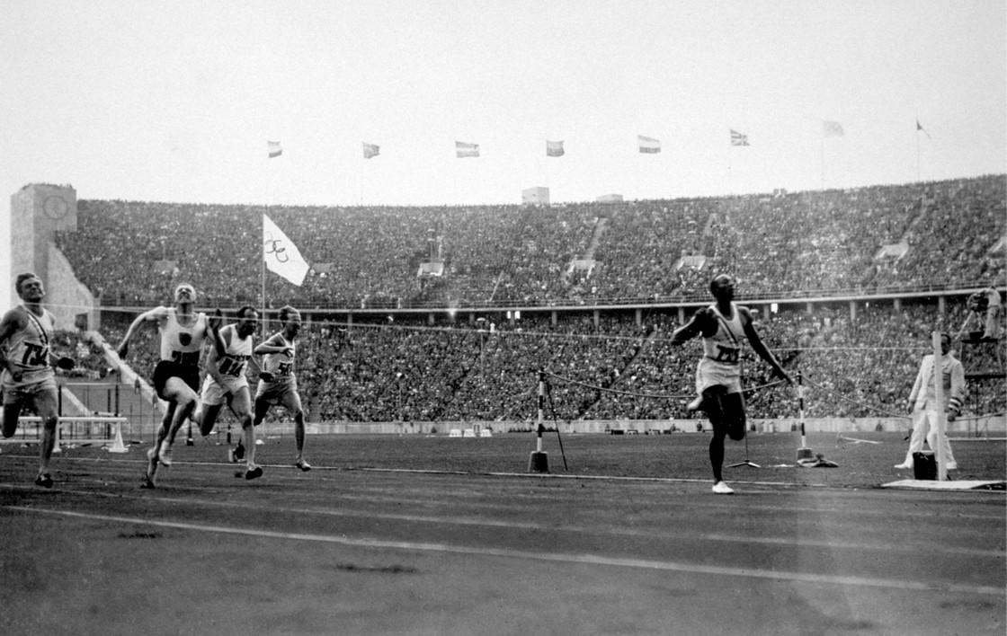 Jesse Owens cruzando a linha de chegada em Berlim para vencer os 100 metros rasos em 3 de agosto de 1936
