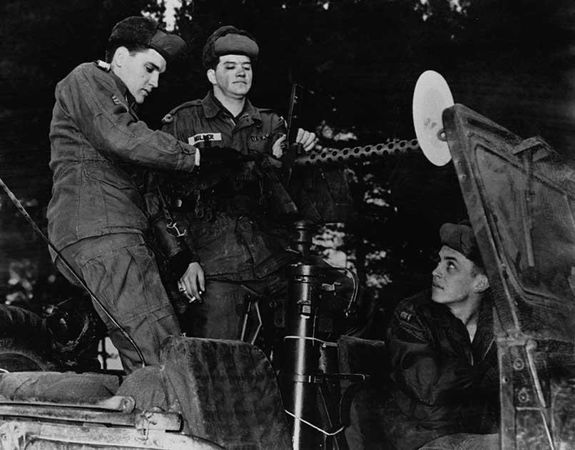 Em março de 1958, Elvis Presley foi convocado para o Exército dos EUA como soldado. Um frenesi da mídia invadiu o campo de treinamento. Aqui Presley aparece operando uma arma