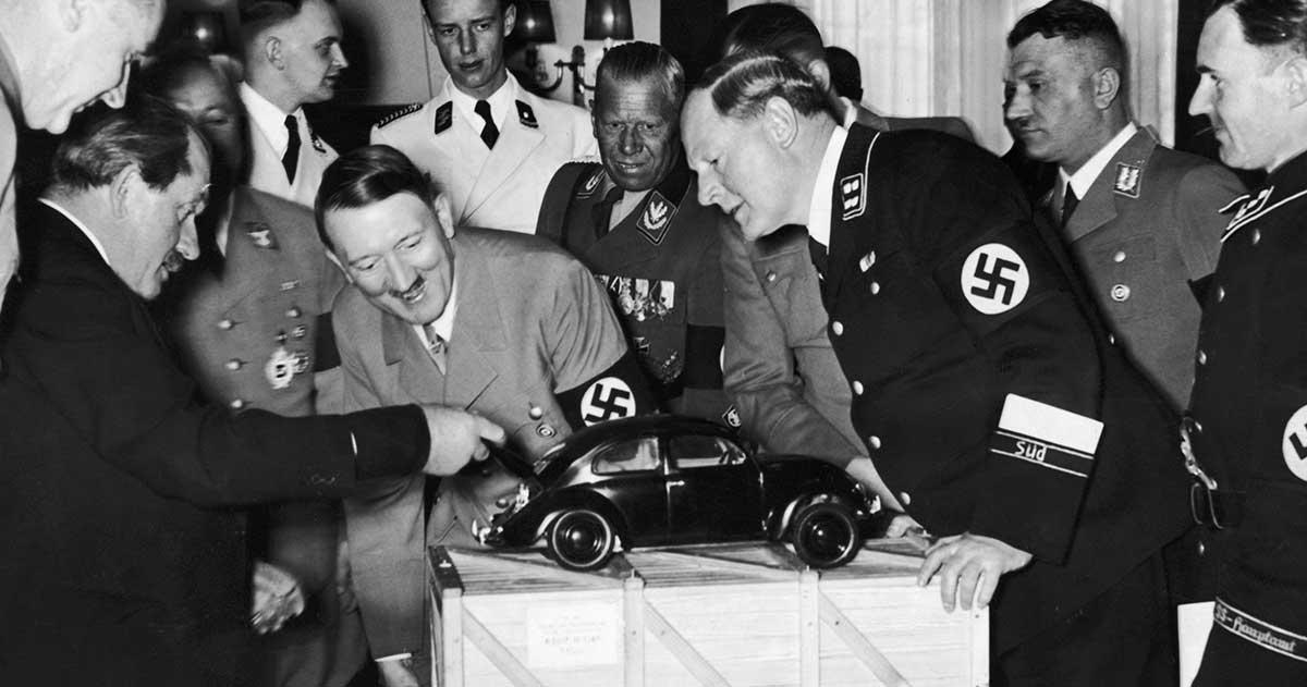 Ferdinand Porsche (esquerda) diverte o ditador alemão Hitler, mostrando-lhe um modelo de Fusca
