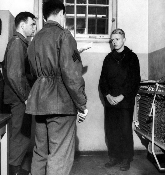 K. Punzeller, membro de 16 anos da Juventude Hitlerista, ouve um sargento americano traduzir sua pena de prisão perpétua por espionagem, em 1945. A Juventude Hitlerista era uma instituição obrigatória para jovens da Alemanha nazista, que visava treinar crianças e adolescentes alemães de 6 a 18 anos de ambos os sexos para os interesses nazistas. Os jovens se organizavam em grupos e milícias paramilitares