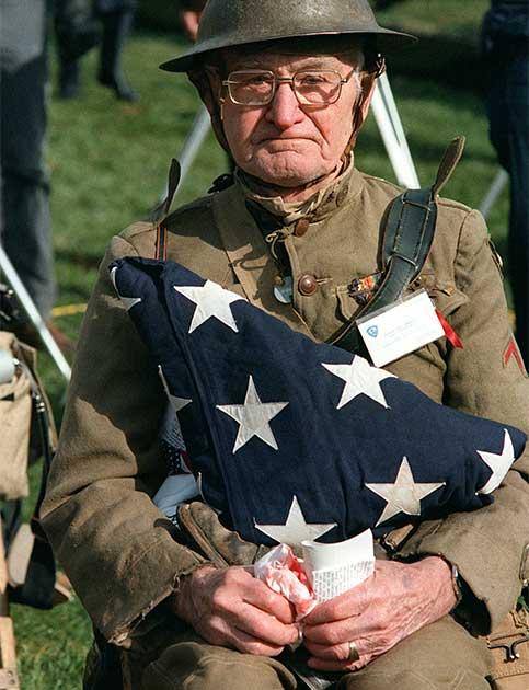 Joseph Ambrose, veterano da Primeira Guerra Mundial, acompanhando uma cerimônia oficial no Memorial dos Veteranos do Vietnã, em Washington DC, em 1982. Ambrose segura a bandeira que cobria o caixão do filho que morreu na Guerra da Coreia em 1951