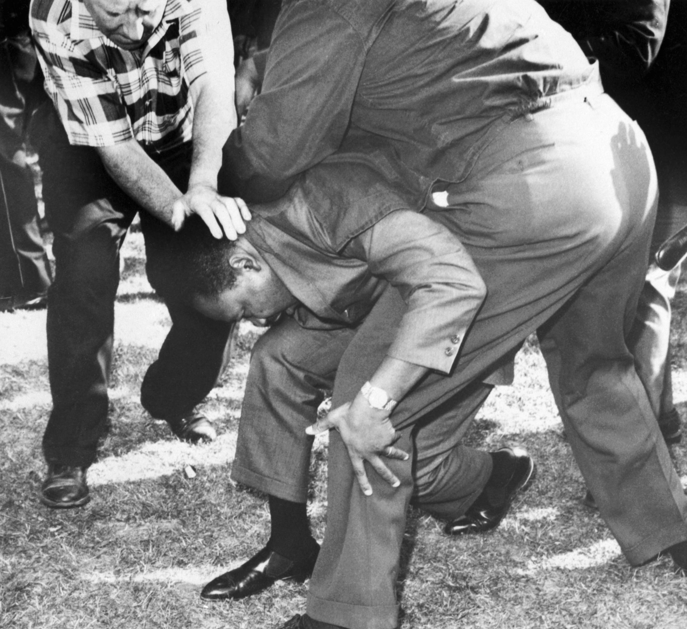 Martin Luther King Jr protegido por assessores no meio de uma multidão hostil. Durante a marcha ele foi atingido por uma pedra na cabeça