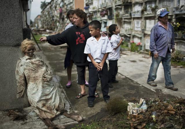 Corpo exumado de seu túmulo e deixado apoiado na parede, num cemitério da Guatemala, após parentes não conseguirem pagar as taxas do cemitério