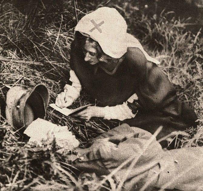 Enfermeira da Cruz Vermelha anota  as últimas  de um soltado britânico, 1917