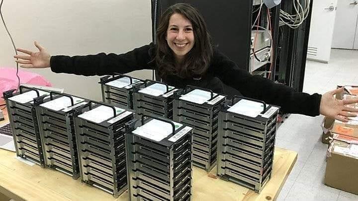 Katie Bauman posando com os 5 petabytes de dados necessários para a imagem de um buraco negro