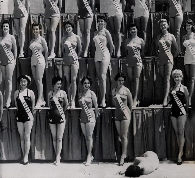 Todo mundo sorrindo, enquanto a Miss Nova Zelândia está desmaiada no chão durante uma sessão de fotos do concurso Misso Universo, em 1954