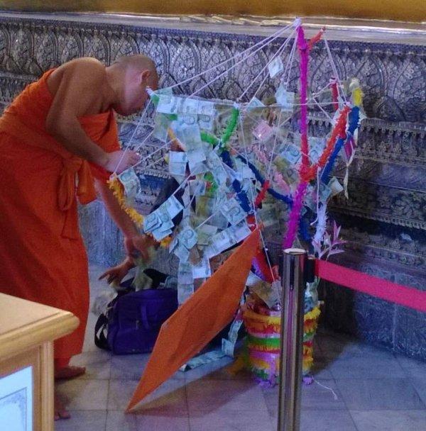 Monges tailandeses decoram árvore de dinheiro com notas. Ninguém se atreve a mexer no dinheiro
