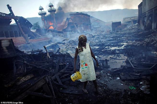 Mulher percorrendo o que sobrou do mercado de Port-au-Prince, Haiti, em 29 de janeiro de 2010. Um terremoto de magnitude 7 atingiu a ilha do Caribe duas semanas antes, matando 300 mil pessoas
