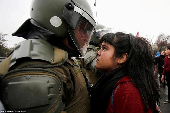 Manifestante encara furiosamente um policial de choque durante protestos em Santiago, marcando o golpe militar de 1973, no Chile
