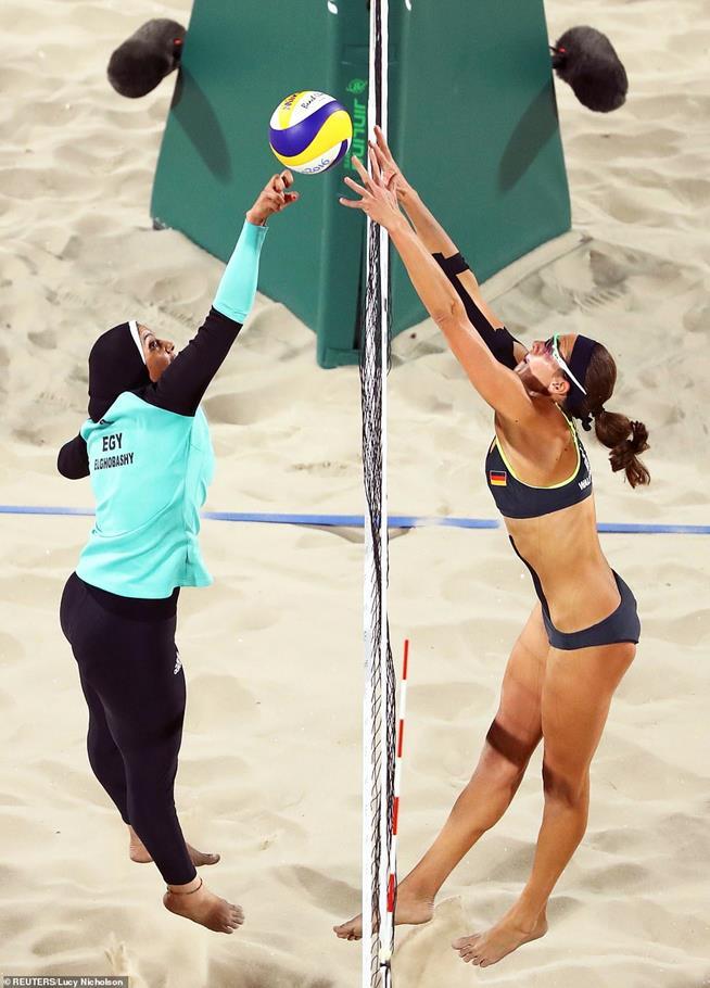 Doaaa Elghobashy, do Egito e Kira Walkenhorst, da Alemanha, mostram as diferenças de uniformes e culturais durante partida de vôlei de praia nos Jogos Olímpicos do Rio, em 2016