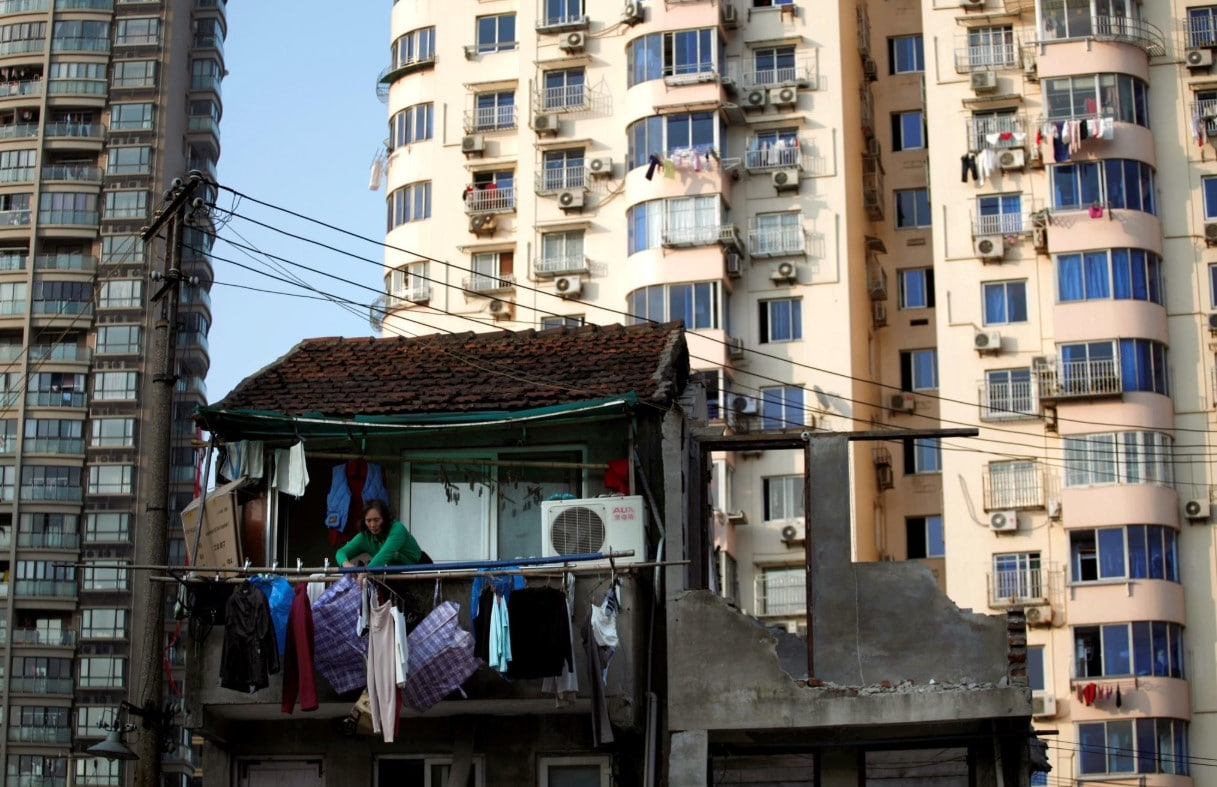Mulher na varanda da sua casa, que será demolida para construção de novos prédios, Xangai, China, 1 de dezembro de 2010