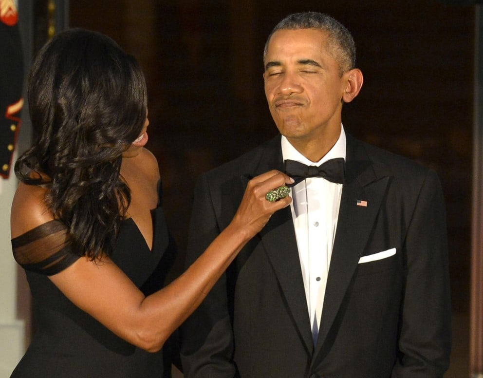 A então primeira-dama Michelle Obama ajeita a gravada de Barack Obama antes da chegada do presidente chinês Xi Jinping à Casa Branca