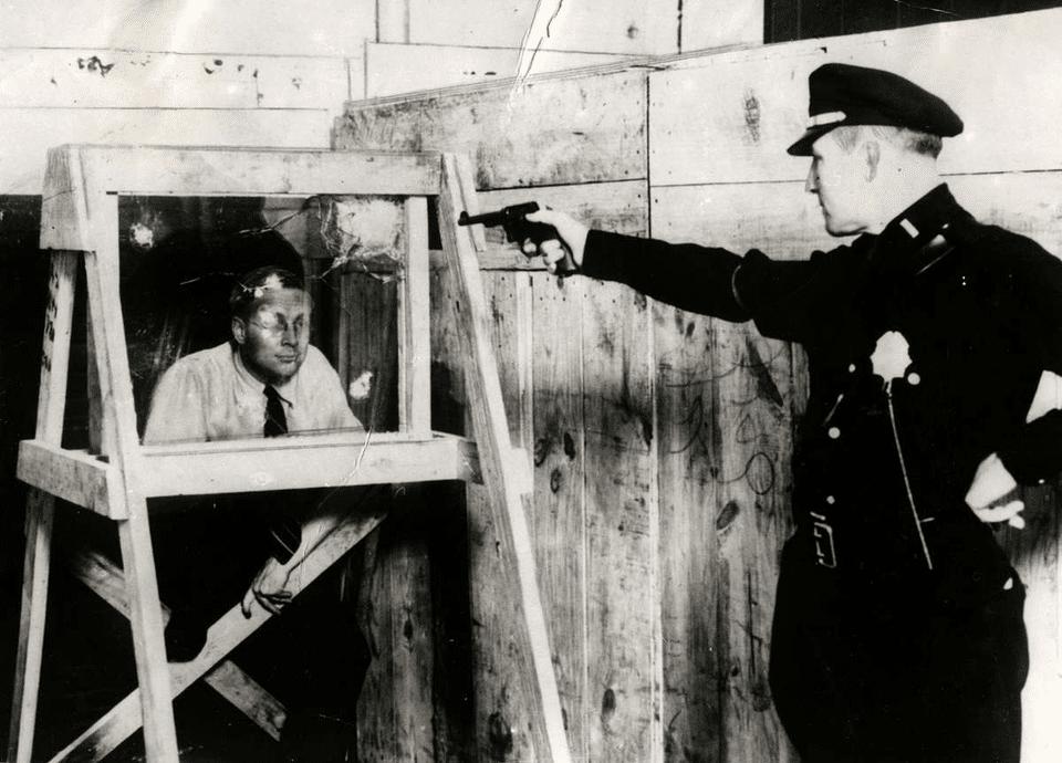 Policial novaiorquino dispara seu 38 contra um homem para comprovar que o vidro à prova de balas realmente funciona, em 1931