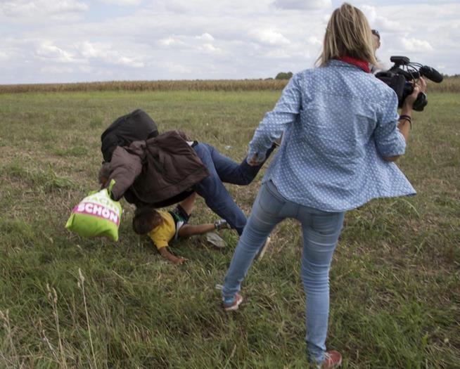 Petra Laszlo, câmera da N1TV, coloca o pé e derruba um migrante que levava uma criança nos braços tentando fugir das autoridades em Roszke, na Hungria. Ela foi demitida pela emissora