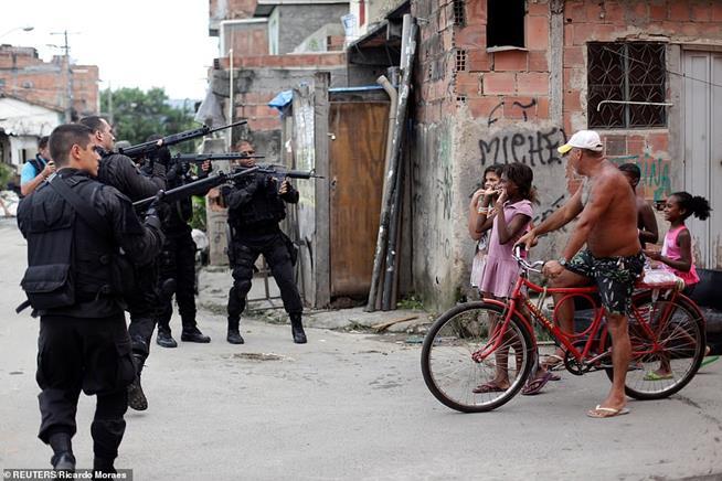 Moradores da favela da Maré, no Rio de Janeiro, observando policiais durante programa de pacificação, em 26 de março de 2014