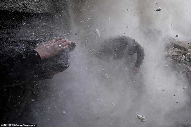 Rebeldes sírios esquivam-se dos escombros depois que um muro que usavam como barreira foi atingido por uma bala disparada por combatentes do governo, em Damasco, Síria, em 30 de janeiro de 2013
