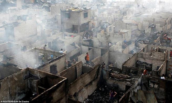 Moradores vasculham as ruínas de suas casas após incêndio na cidade de Makati, Manila, Filipinas. O incêndio, ocorrido em 19 de abril de 2011, foi iniciado por um curto-circuito e rapidamente se espalhou atingindo dezenas de casas