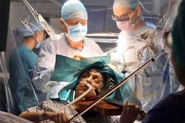 Membro da Orquestra Sinfônica de Isle of Wight durante cirurgia para remoção de tumor cerebral potencialmente fatal. Para garantir que a música não perdesse funções motoras vitais, ela tocou violino enquanto o tumor era removido