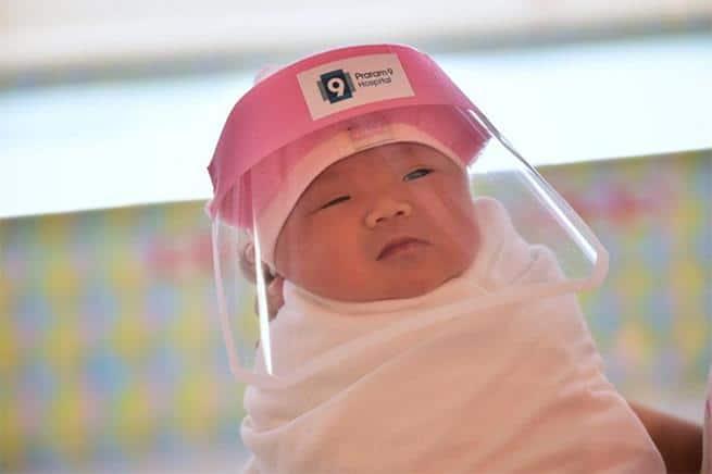 Bebês recém-nascidos na Tailândia são equipados com protetores faciais para evitar contaminação com coronavírus