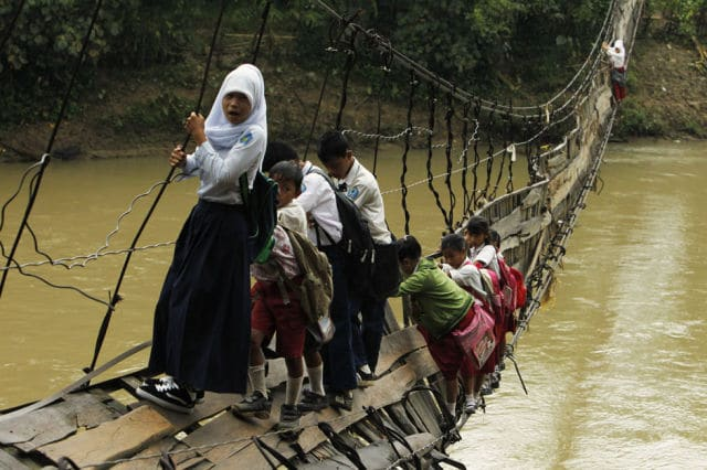 Estudantes seguram nas barras laterais de uma ponte que desabou sobre um rio na aldeia de Sanghiang Tanjung, na Indonésia, em 19 de janeiro de 2012