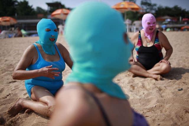 Mulheres vestindo máscaras de nulon na costa da província de Shandong, em 6 de julho de 2012. A máscara foi inventada há 7 anos para bloquear os raios do sol