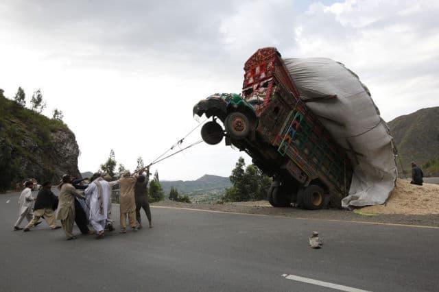 Homens usam cordas para tentar resgatar caminhão e suprimento de trigo, no distrito de Malakand, noroeste do Paquistão, em 13 de abril de 2012