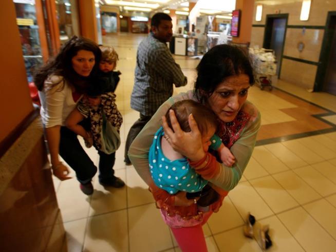 Mulheres levam crianças para um local seguro enquanto atirador responsável por um tiroteio num centro comercial de Westgate, Nairobi, é procurado. Foram 39 mortos e 150 feridos. Quênia, 21 de setembro de 2013