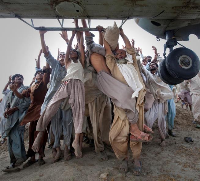Pessoas afetadas por inundação no Paquistão agarram-se a helicóptero que distribuía comida na província de Punjab. Agosto de 2010