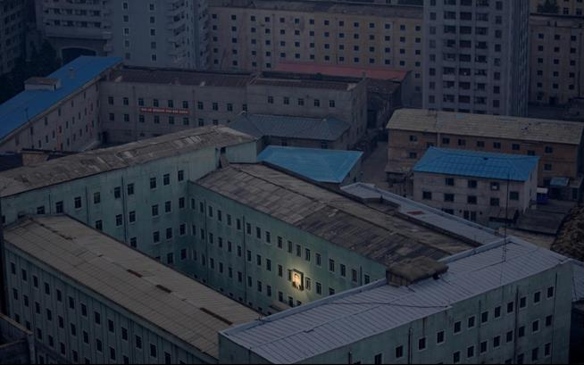 Fotografia do líder da Coreia do Norte, Kim Il-sung, ilumina a fachada de um edifício na capital de Pyongyang. O rosto dele acompanha os cidadãos da capital norte-coreana em cada canto e edifício