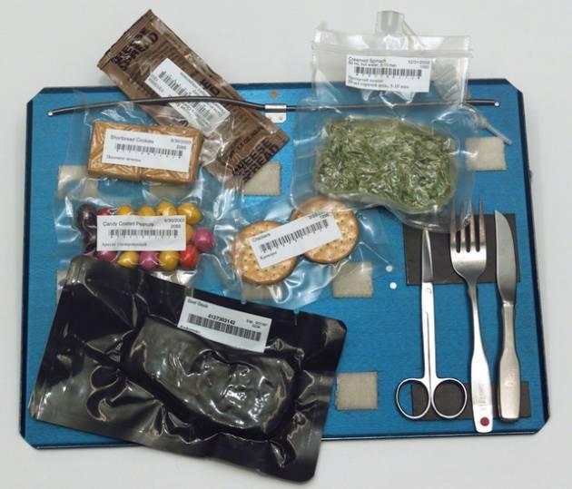 Bandeja com alimentação servida a astronautas. Tudo fica preso por imãs e velcros