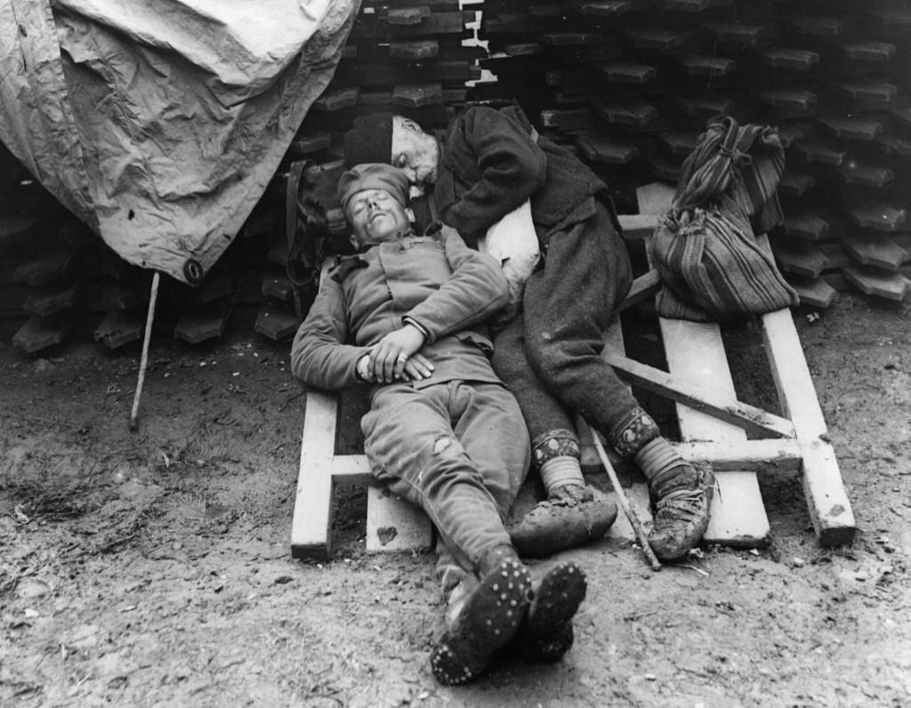 Soldado sérvio dorme ao lado do pai, que foi visitá-lo na linha de frente perto de Belgrado, 1915