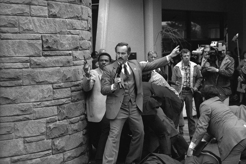 Agente do Serviço Secreto empunhando uma metralhadora enquanto outros agentes e a polícia dominam o atirador John Hinckley Jr, lá atrás. Hinckley atirou no presidente Reagan em Washington em 30 de março de 1981