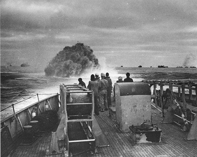 Homens da guarda costeira dos EUA observam quando uma de suas cargas de profundidade atinge submarino alemão U-175 no Atlântico, em 1943