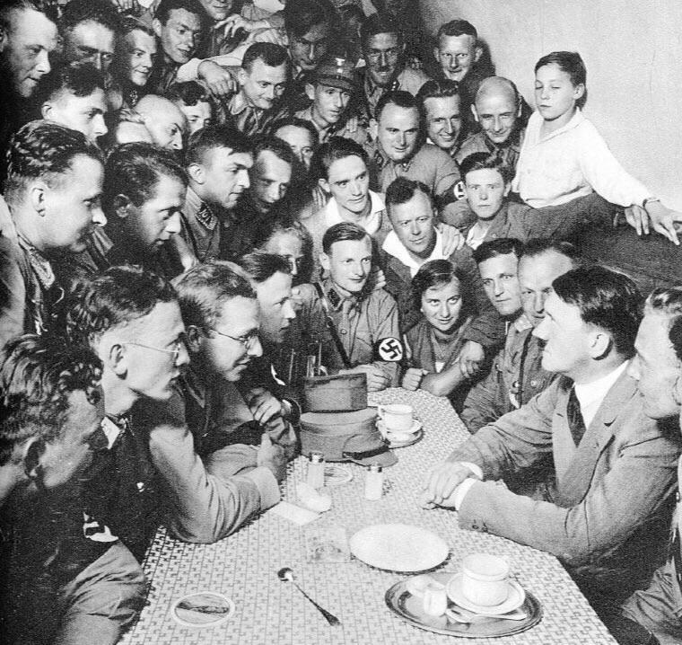 Hitler rodeado por correligionários nazistas em uma mesa, em Berlim, 1933.