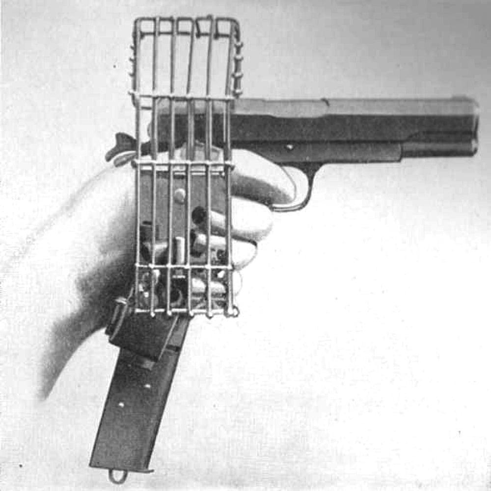 Pistola US. 45 cal M1911 com carregador estendido e gaiola de latão. Nos primeiros dias da Primeira Guerra Mundial, as aeronaves não tinham metralhadoras e os pilotos atiravam uns nos outros com pistolas. A gaiola evitava que os projéteis caíssem no piso da cabine e interferissem no trabalho dos pilotos
