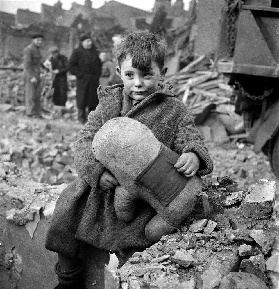 Menino segurando um bicho de pelúcia em meio a ruínas após bombardeio aéreo alemão de Londres, 1945