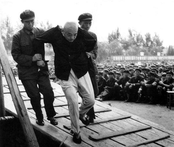 Marechal chinês Peng Dehuai, que comandou o exército chinês durante a Guerra da Coréia, sendo conduzido pelos Guardas Vermelhos para uma cerimônia pública de humilhações em Pequim, durante a Revolução Cultural, 1960