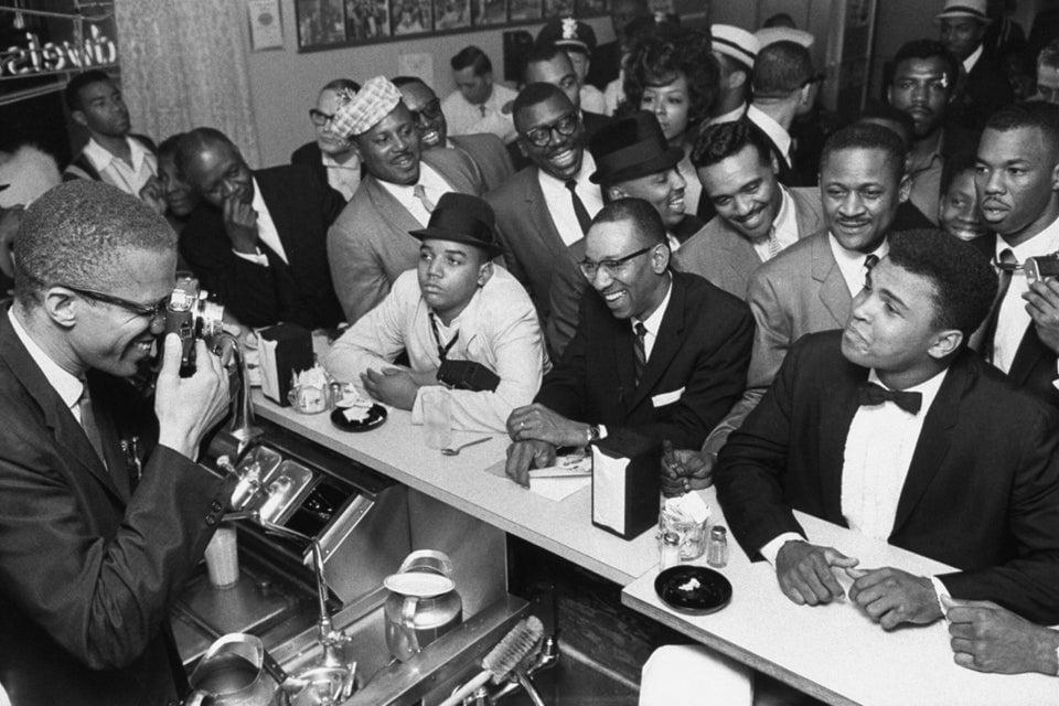 Muhammad Ali (à direita) posando para uma foto tirada por Malcolm X (à esquerda) em Miami, depois de ganhar o título dos pesos pesados contra Sonny Liston, 1964