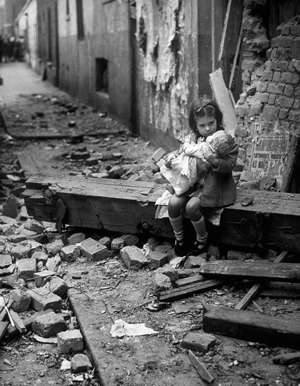 Menina sentada nas ruínas de sua casa bombardeada durante a Batalha da Grã-Bretanha - 24 de agosto de 1940