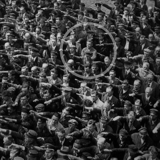 O homem que recusou-se a fazer a saudação nazista é August Landmesser. Ele se juntou ao partido nazista em 1931, acreditando que isso o ajudaria a conseguir um emprego durante crise econômica. No entanto, em 1934, Landmesser apaixonou-se por uma mulher judia. Um ano mais tarde, eles ficaram noivos, mas seu pedido de casamento foi negado pelas leis de Nuremberg, que proibia casamentos entre judeus e não judeus.