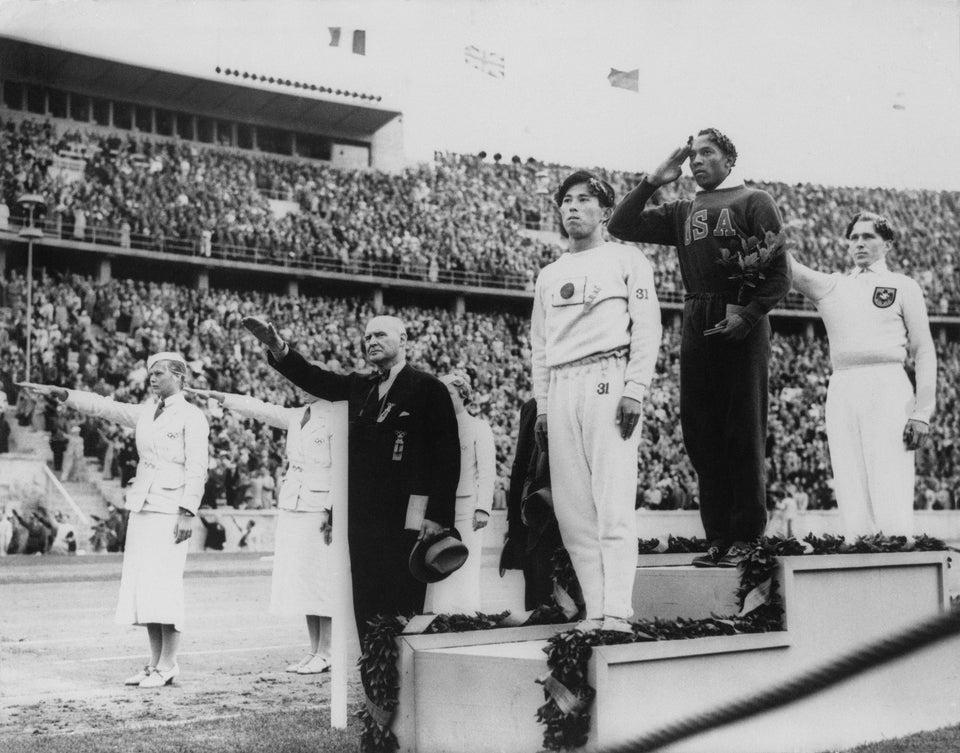 Jesse Owen (EUA) durante premiação após terminar em 1º lugar no salto em distância nos Jogos Olímpicos de Verão de 1936, realizados em Berlim, com Luz Long (Alemanha) em 2º e Naoto Tajima (Japão) em 3º lugar.
